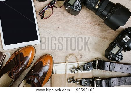 Photography hipster work table set with tablet, film, vintage shoes, lenses, supplies and digital film cameras. Top view with copy space, vintage flat lay
