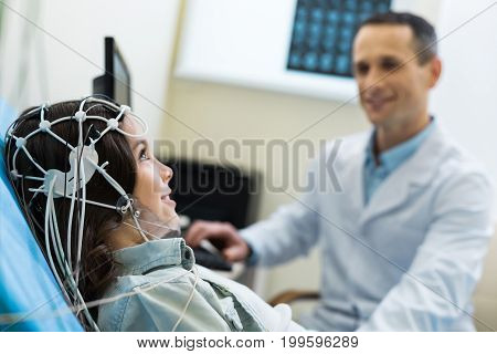 Careful examination. The focus being on a beautiful young woman undergoing electroencephalography carried out by a pleasant medical specialist in a lab