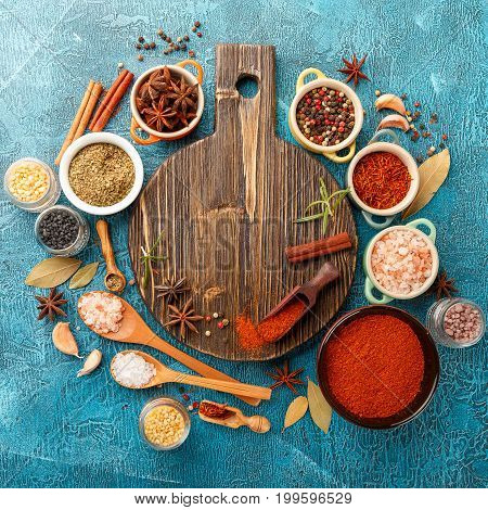 Dry colorful spices and condiments anise, paprika, saffron, pepper, salt, bay leaf, cinnamon in small bowls on blue background. Top view