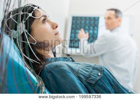 Vital procedure. Beautiful dark-haired woman lying on an examination table and undergoing electroencephalography while her doctor examining CT results