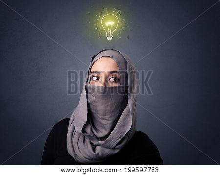 Young muslim woman wearing niqab with lit lightbulb above her head