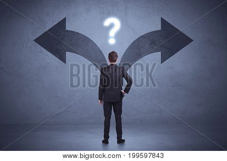 Businessman taking a decision while looking at arrows on the wall concept background