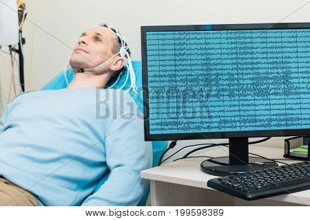 Accurate data. Charming young man lying on the examination table with electrodes on his head while the computer displaying his brain waves