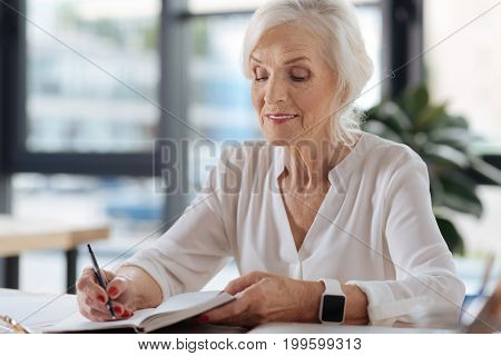 My memories. Joyful delighted senior woman sitting at the table and writing her memoirs while being in the cafe