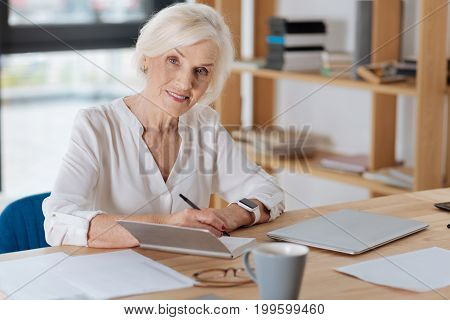 Chief executive. Delighted positive aged businesswoman sitting at the table and smiling while working at the office