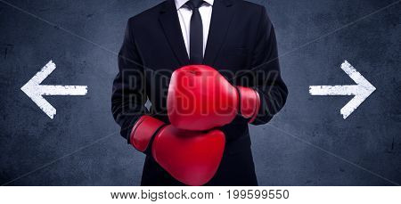 A confident businessman standing with red boxing gloves on his hand in front of arrows pointing in different directions on urban wall background concept.