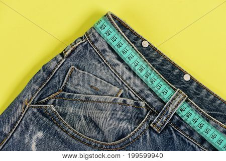 Top Part Of Denim Trousers Isolated On Yellow Background.