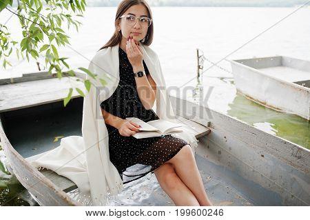 Portrait Of An Attractive Woman Wearing Black Polka Dots Dress, White Shawl And Glasses Reading A Bo
