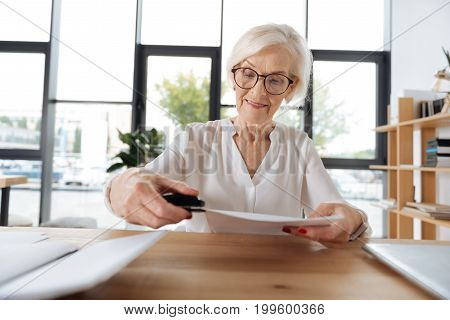 Office stationery. Joyful nice senior woman sitting at the table and using a stapler while working with documents