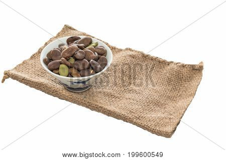 Many broad beans in a cup placed on a cloth sack .