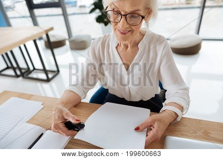 Office documents. Positive delighted aged woman holding a stapler and smiling while working with office documents