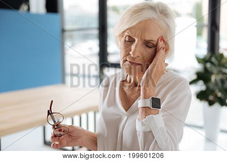 I feel headache. Unhappy serious senior woman holding her temple and feeling a headache while being tired from work