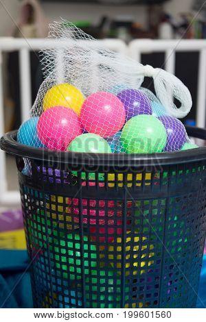 Colorful toy balls in mesh bag on black basket