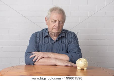 Mature man with a concerned expression, looking at a piggy bank