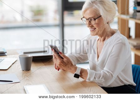 Pleasant message. Cheerful positive nice woman looking at her smartphone screen and smiling while receiving a pleasant message