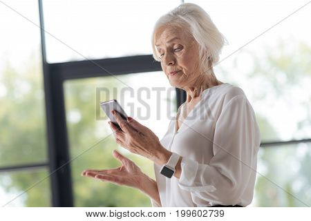 It doesnt work. Unhappy smart senior woman looking at her phone and being irritated while not being able to make a call