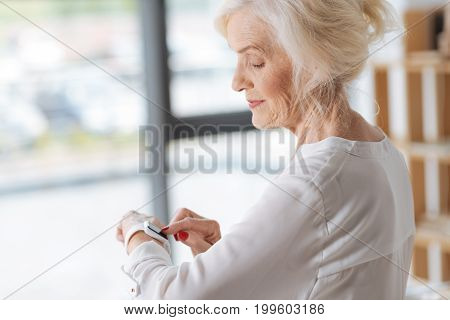 Wearable technologies. Joyful positive elderly woman holding her hand and touching the sensory screen while using a smartwatch