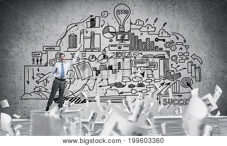 Businessman keeping hand with book up while standing among flying papers with business-plan information on background. Mixed media.