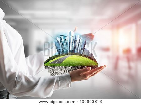 Cropped image of business woman in shirt keeping green island with metropolis city in her hands with office view and sunlight on background. Mixed media.