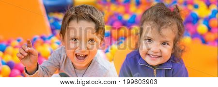Adorable smiling little girl and boy. Portrait. Happy child playing with color balls. Summer day. Funny cute child making vacations and enjoying summer. Concept for advertising poster children's playground.