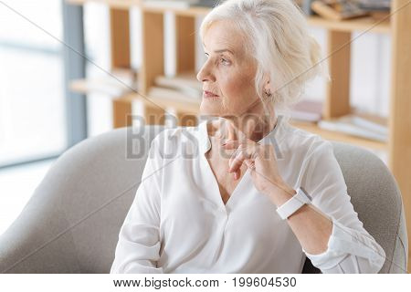 Thoughtful look. Smart pleasant thoughtful woman looking aside and thinking about her life while sitting in the armchair
