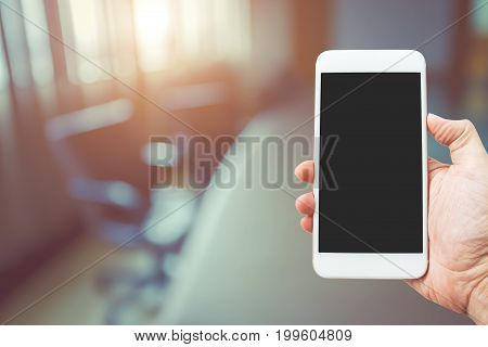 Hand holding mobile smart phone with blank screen concept of business team meeting present and new startup project. Digital tablet laptop computer design smart phone using.
