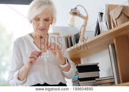 Strong painkillers. Unhappy ill elderly woman standing in her room and taking pills while suffering from pain