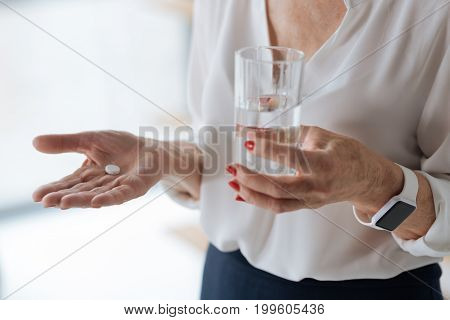 For headache. Close up of a painkiller pill with a glass of water being held by a pleasant nice aged woman