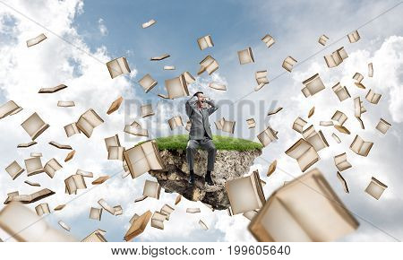 Young shocked businessman sitting on green floating island and covering eyes with palms