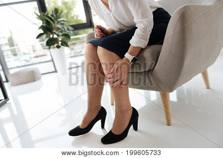 After work. Close up of a nice tired aged woman holding he legs and feeling pain while coming home after work