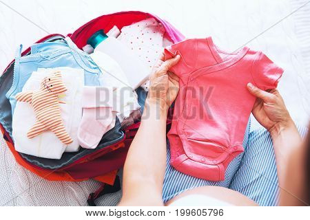 Pregnant woman packing suitcase bag for maternity hospital at home getting ready for newborn birth labor. Pile of baby clothes necessities and pregnant women at awaiting.
