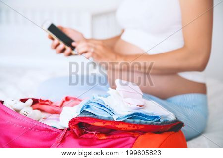 Pregnant woman packing for hospital and taking notes in smart phone getting ready for newborn birth labor. Pile of baby clothes necessities and pregnant women at awaiting.