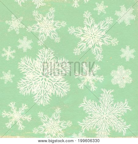 Christmas background with old paper texture of green color and snowflakes