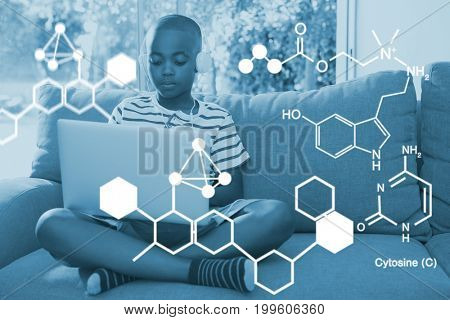 Digitally generated image of chemical structure against boy using laptop while listening to headphones at home