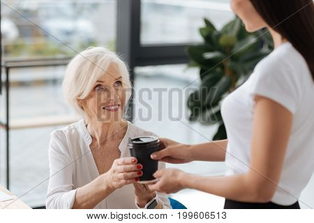 Favourite drink. Delighted positive aged woman taking a cup with coffee and smiling while being in a good mood