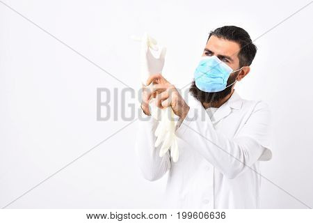 Medical worker with blue medical mask. Medical worker putting on white gloves isolated on white background copy space. Physician with beard in white gown. Medicine and health concept