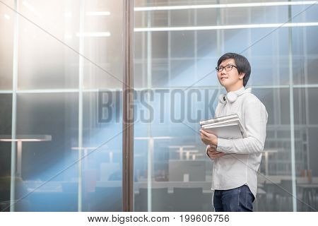 Young Asian man university student holding books in library study and learning with international education lifestyle concepts