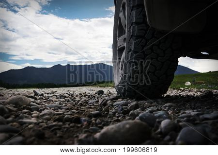 Off-road travel on mountain road. The wheel of the SUV in the foreground on the stone road of gravel.