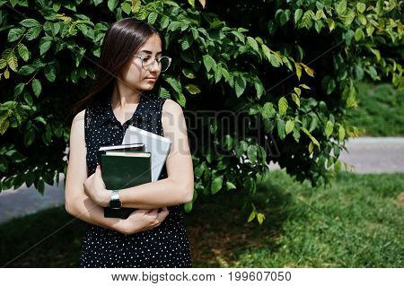 Portrait Of A Shy Young Woman In Black Polka Dot Dress And Glasses Holding Books In The Park.