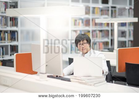 Young Asian man university student working with laptop computer and notebook in library self learning and college lifestyle concepts