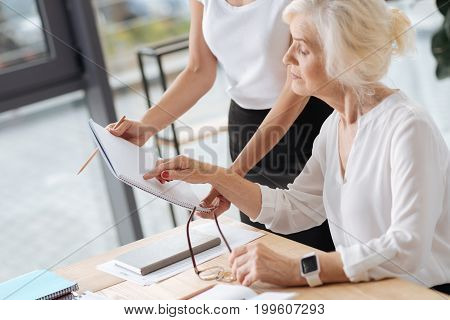 Everything is correct. Intelligent smart elderly woman sitting at the table and reading notes while helping her young colleague