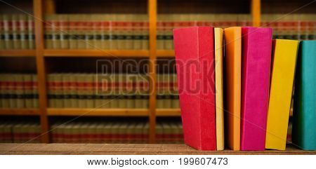Colorful books arranged on table against bookshelf in school