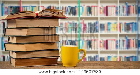 Stack of books by yellow mug on wooden table against multi colored bookshelf in library