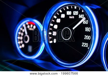 Modern car instrument panel dashboard with blue illuminated display rev up. (Selective focus and shallow depth of field)