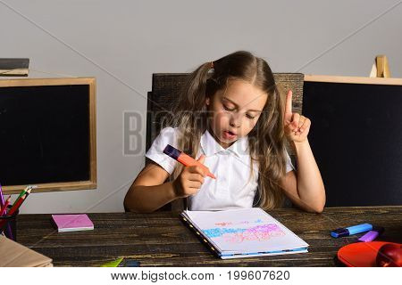 Girl Sits At Her Desk With Colorful Stationery Near Blackboards