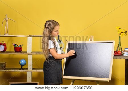 Schoolgirl With Concentrated Face And Ponytails Stands In Classroom