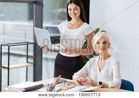 Pleasant cooperation. Nice delighted smart women smiling and looking at you while working together at the office