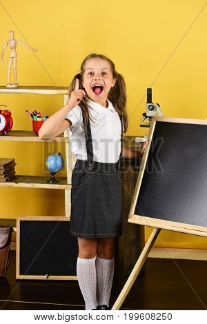 Girl In Classroom Stands Near Blackboard, Copy Space