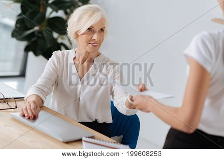 Office documentation. Smart delighted elderly woman looking at her personal assistant and taking documents while sitting at her office