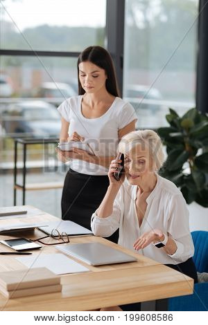 Discussing work. Professional smart senior manager talking on the phone and discussing work while being in the office with her personal assistant